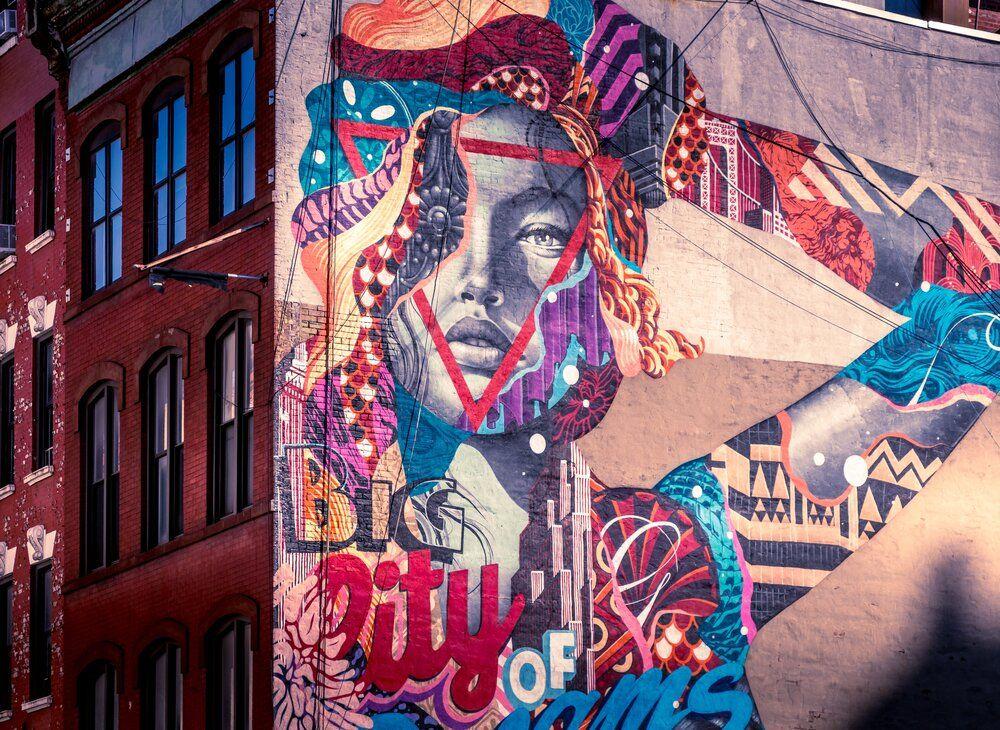 urban mural art of woman posing on side of building